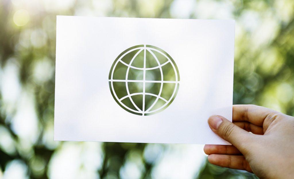 Ein Papier mit ausgeschnittener Weltkugel wird vor einem verschwommenen Hintergrund mit Bäumen gehalten.