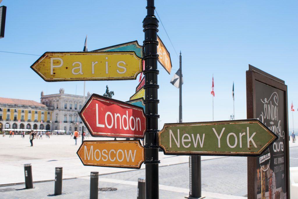 Bunte Wegweiser zeigen in die Richtungen Paris, London, Moscow und New York.