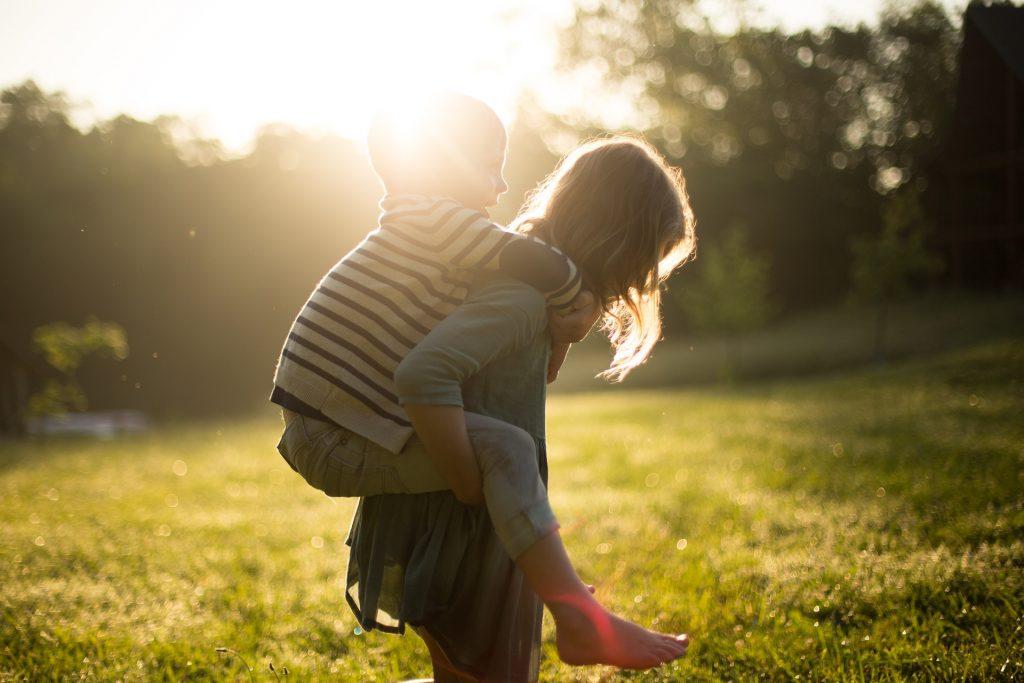 Ein Mädchen trägt einen kleinen Jungen Huckepack.