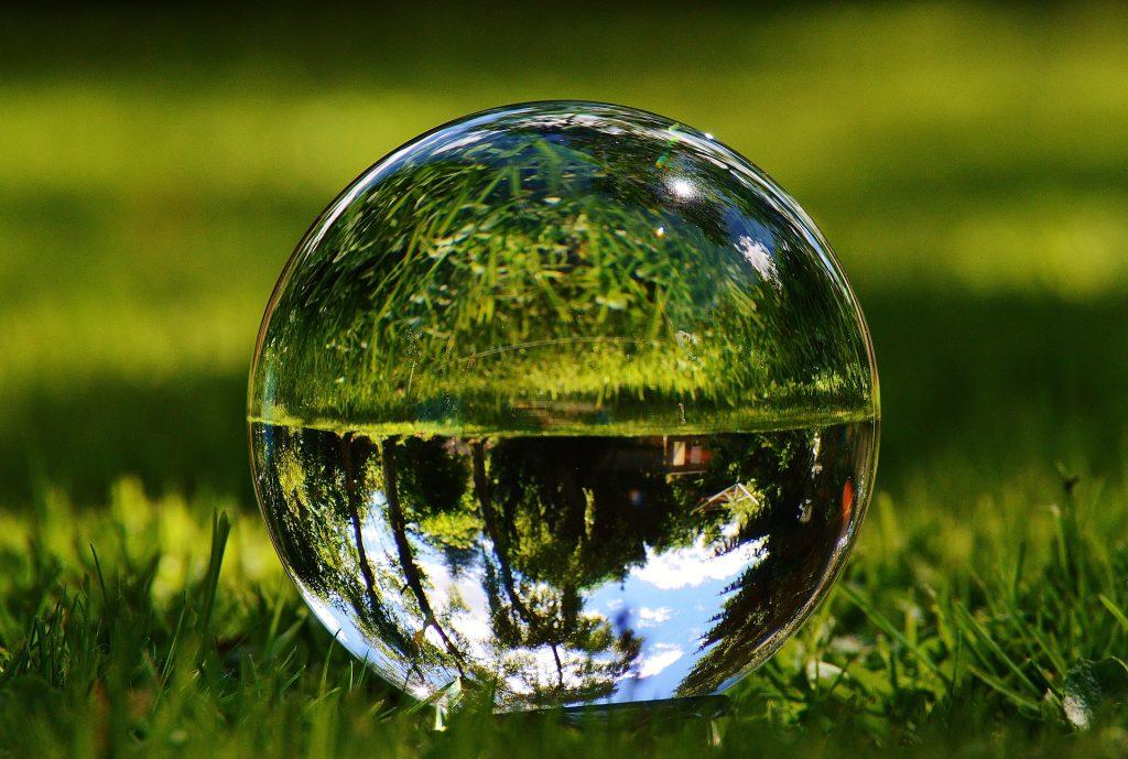 Eine Glaskugel im Gras, in der sich die Umgebung spiegelt.