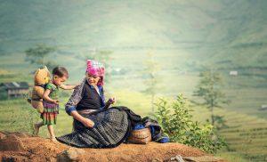 Eine Mutter sitzt zusammen mit ihrem Kind auf einem Berg und macht Pause von der Feldarbeit.
