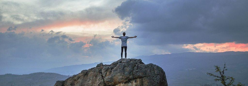 Ein Mann steht mit ausgebreiteten Armen in der Abenddämmerung auf einem Felsen.