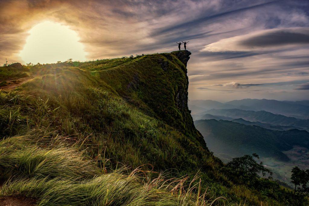 Zwei Personen im Sonnenuntergang stehen auf einem hervorstehenden Felsen und strecken jubelnd die Arme nach oben.