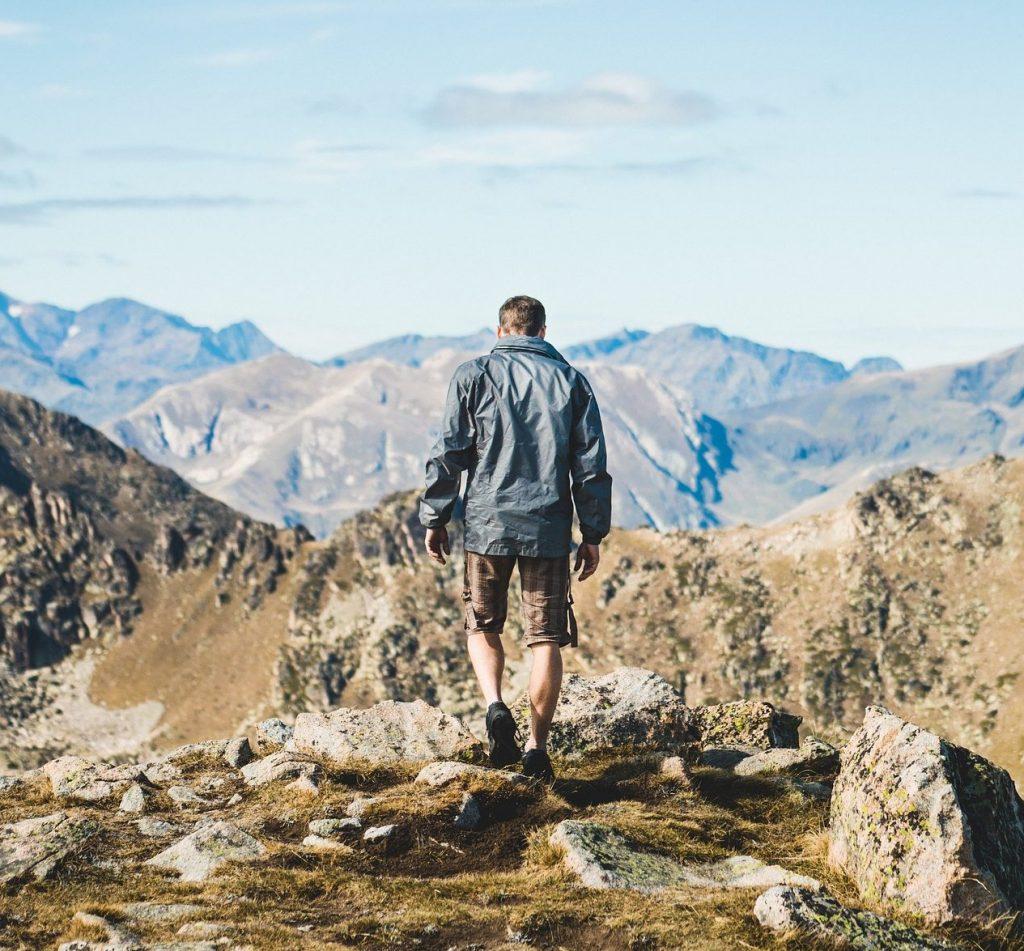 Ein Mann, von Hinten zu sehen, steht auf einem Fels und blickt auf das Gebirge unter ihm.