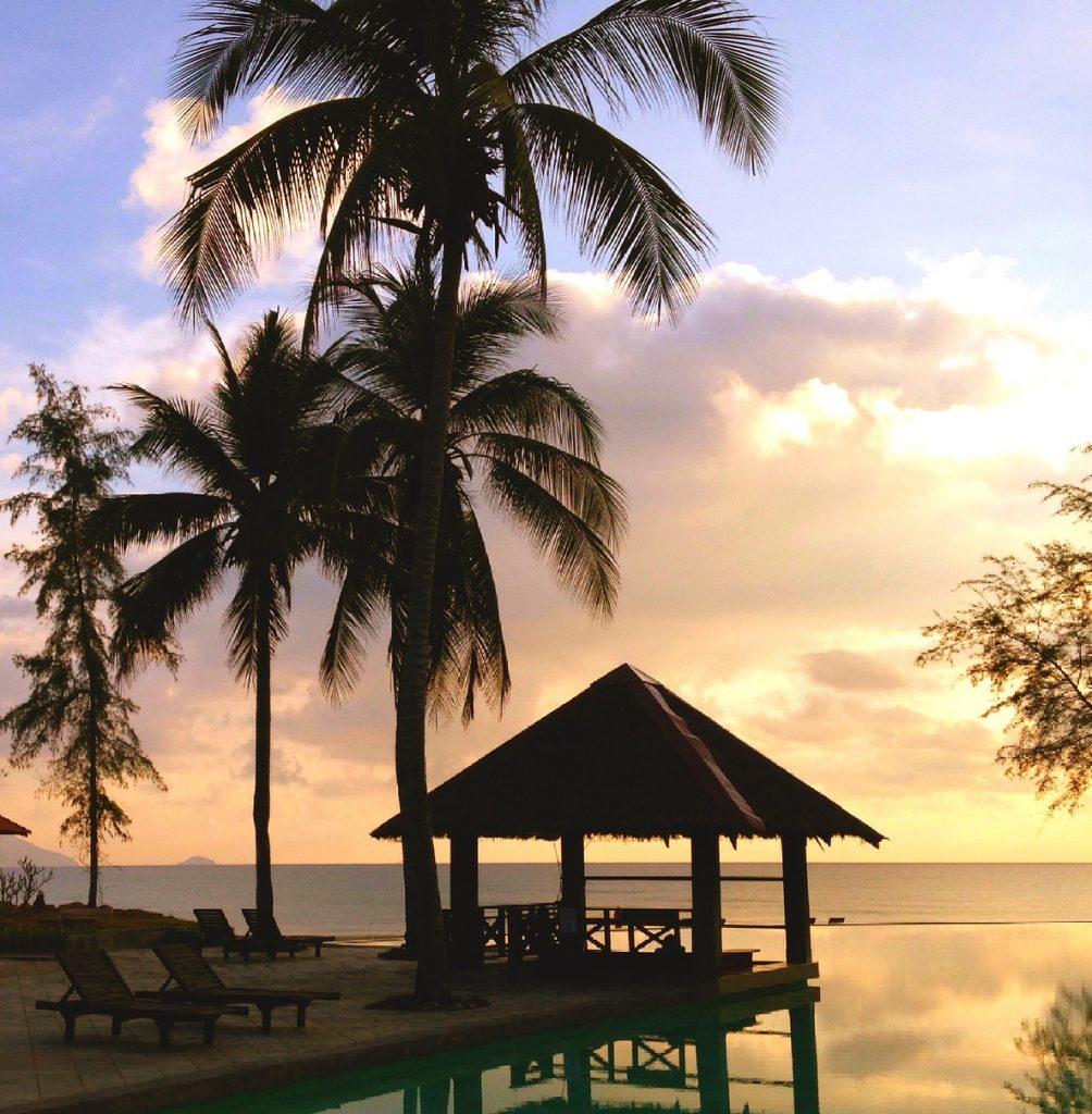 Silhouette von Palmen und einer Bar am Pool im Sonnenuntergang.