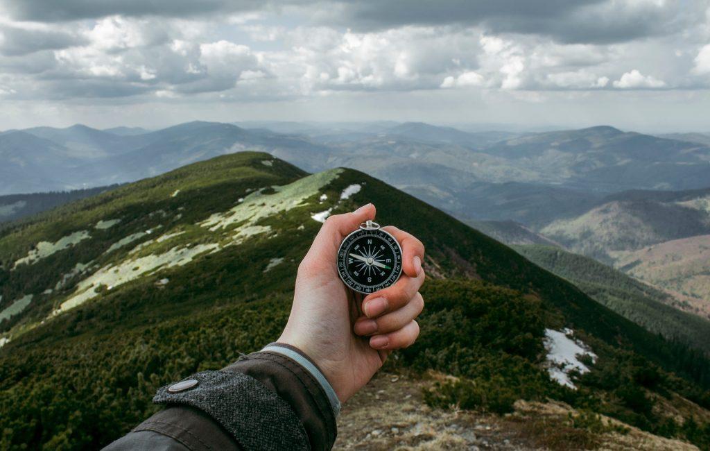 Eine Hand hält einen Kompass vor einem weitläufigen Gebirge.