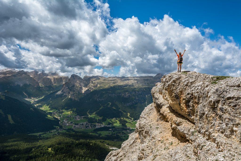 Eine Wanderin steht auf einem Felsen, streckt die Arme nach oben und schaut in das Tal vor ihr.