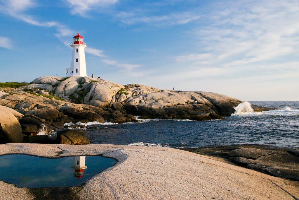 Leuchtturm auf einem Felsen an einer Küste.