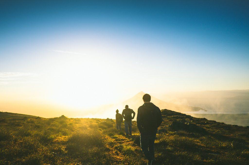 Drei Wanderer gehen eine Wanderweg entlang, dem Sonnenuntergang entgegen.