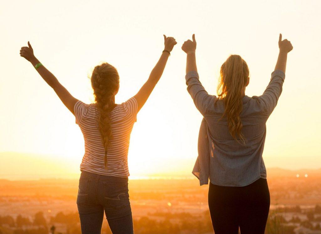 Zwei Frauen stehen mit hochgereckten Daumen auf einem Aussichtspunkt und schauen in den Sonnenuntergang.