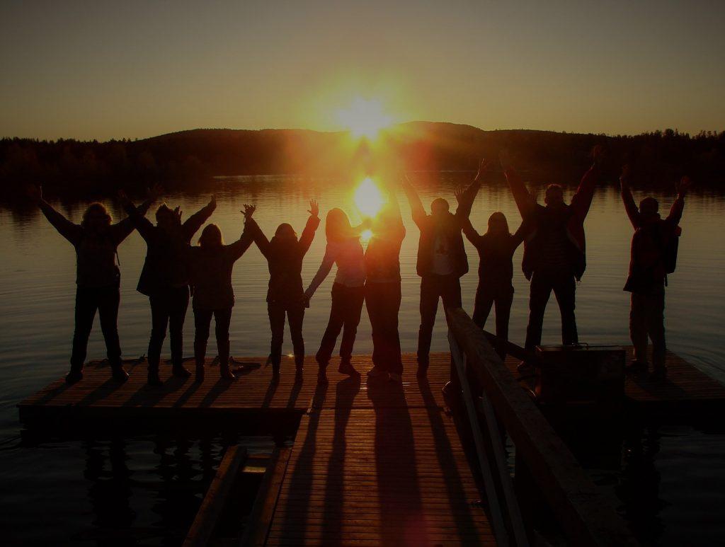 Die Silhouette von einer Gruppe von Menschen, die im Sonnenuntergang auf einem Steg am See stehen und die Arme in die Höhe strecken.