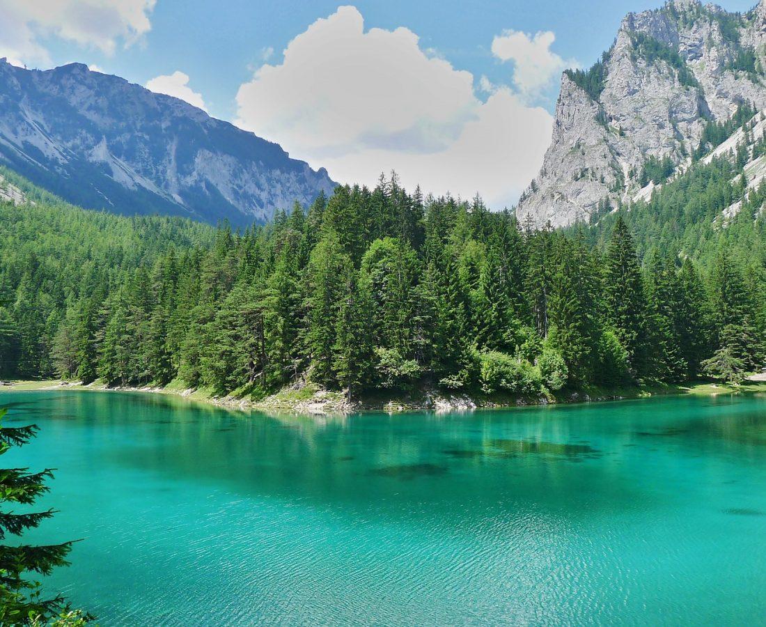 Ein türkiser See im Tal zwischen Wäldern.