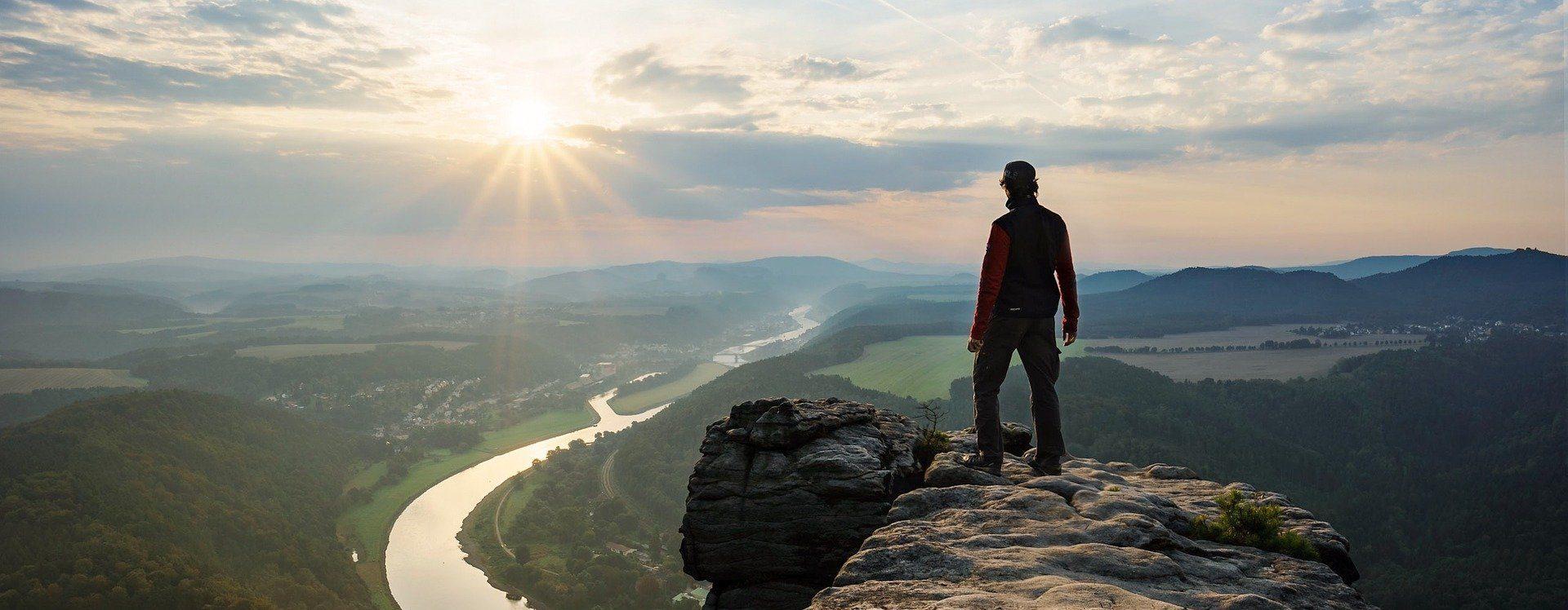 Die Silhouette eines Bergsteigers im Sonnenuntergang, der am Rand eines Felsens steht und in das Tal mit einem Fluss hinab blickt.