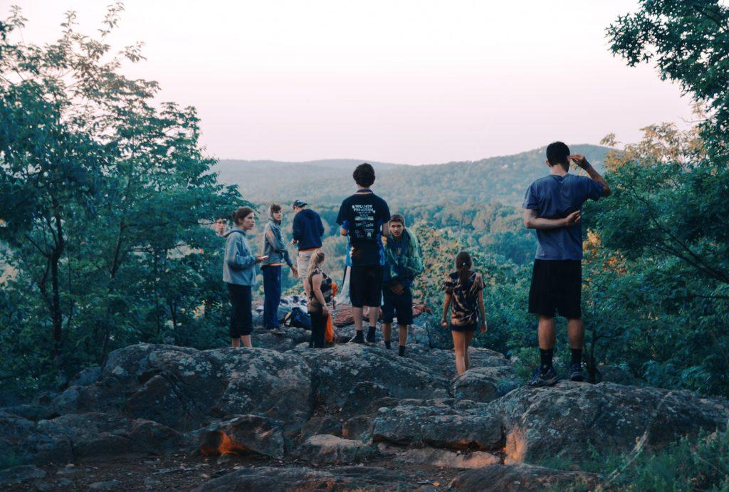 Eine Menschengruppe feiert auf einem Felsen mit Aussicht eine Party.