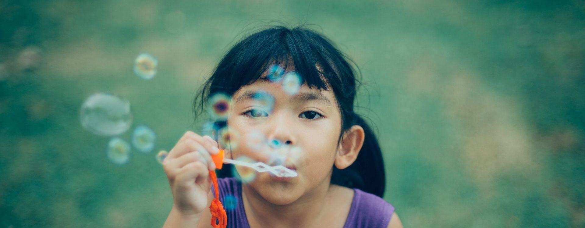 Ein kleines Mädchen pustet Seifenblasen in die Kamera.