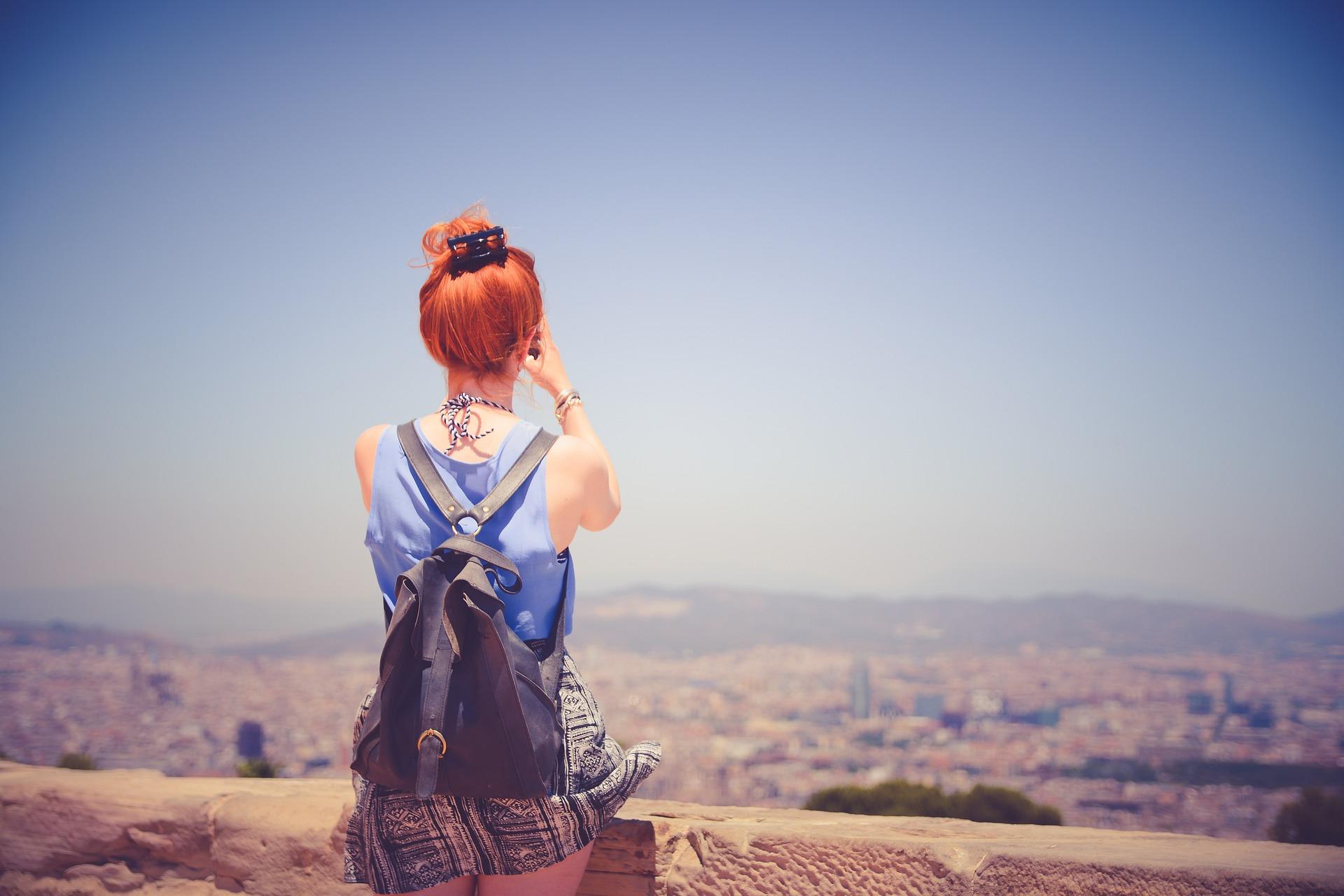 Ein junge Frau steht an einem Aussichtspunkt und fotografiert den Ausblick.
