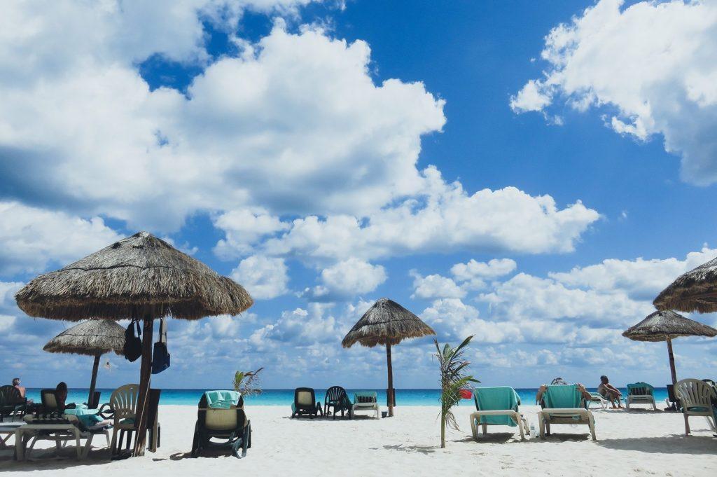Bewölkter Strand mit Sonnenschirmen
