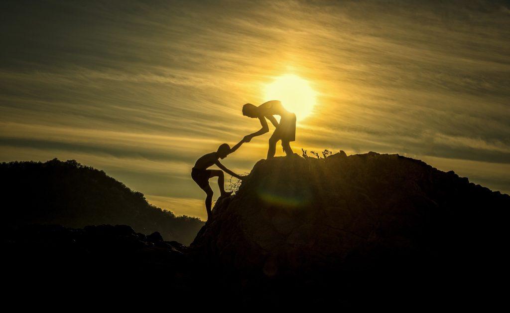 Zwei junge Männer erklimmen einen Gipfel