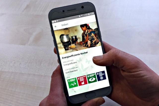 Hände, die ein Smartphone mit der Klima-Kollekte-App zeigen