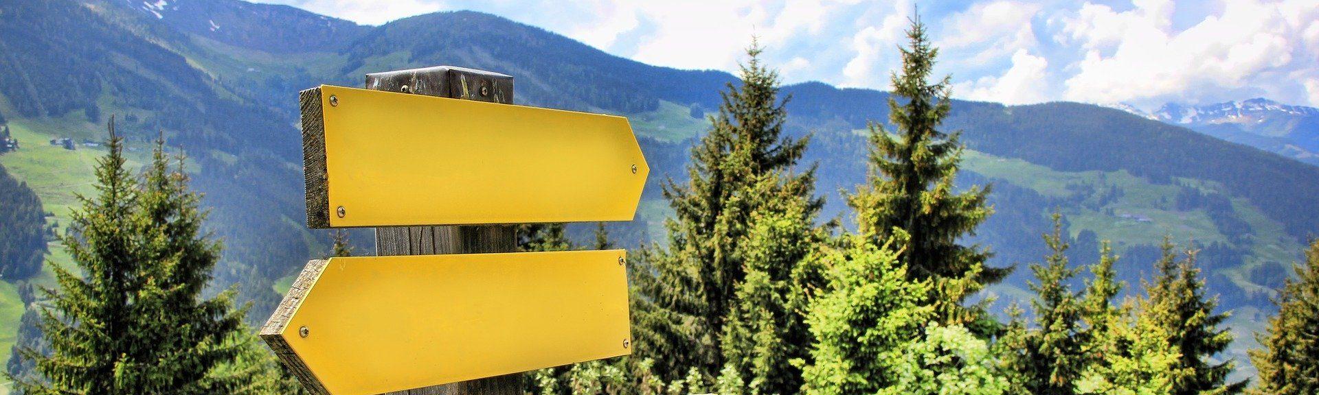 Man sieht zwei Schilder eines Wegweisers in den Bergen.