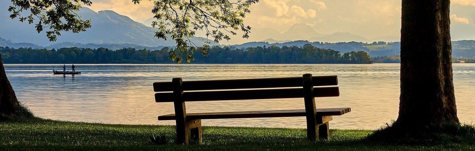 Eine Bank steht vor einem See und die Sonne geht unter.