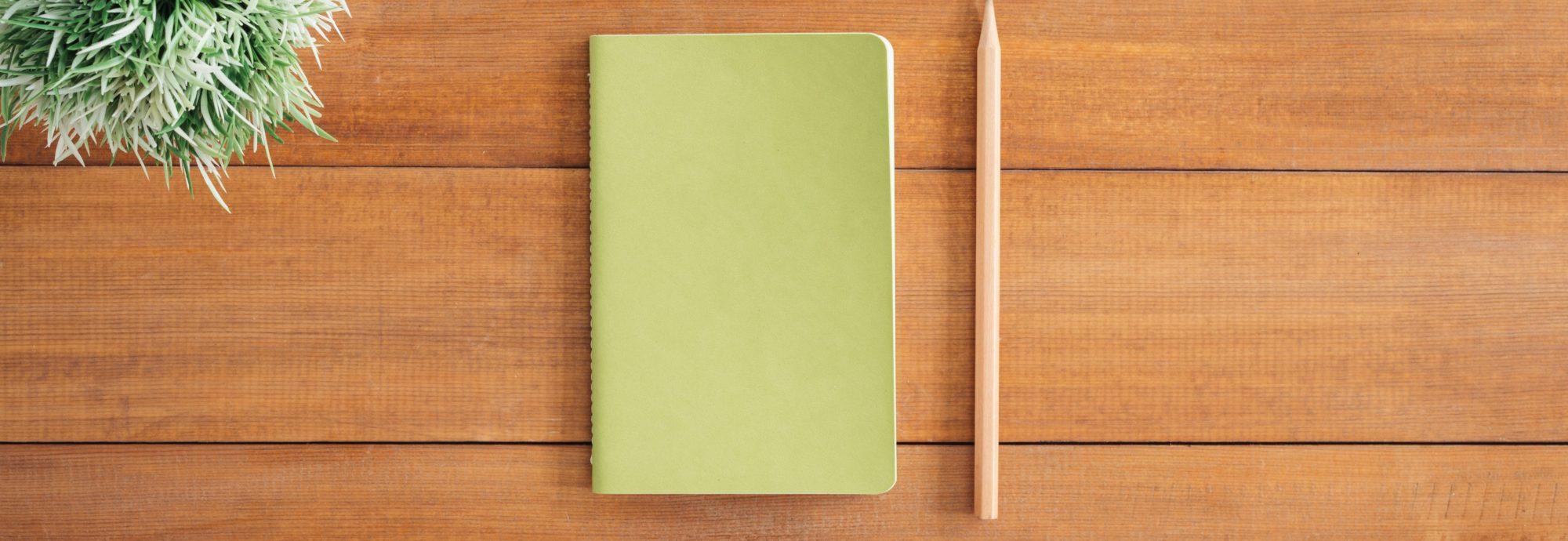 Ein grünes Notizbuch liegt auf einem Holztisch.
