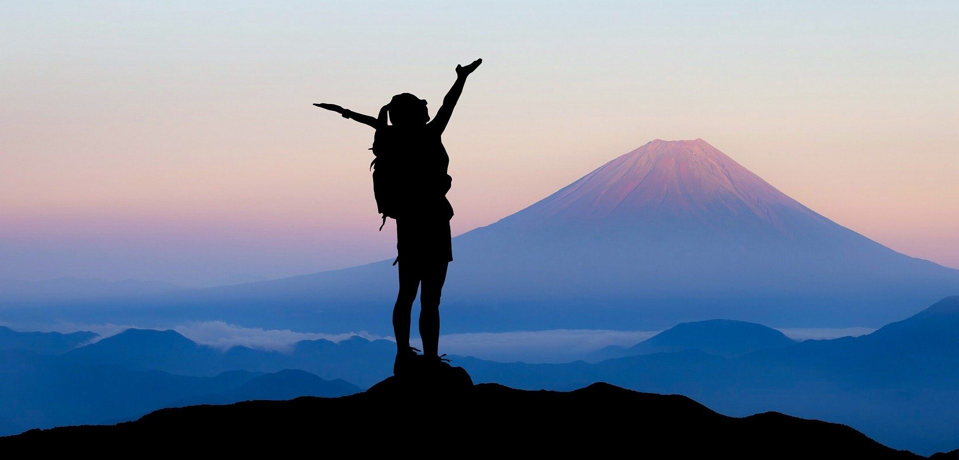 Eine Frau steht auf einem Berg und jubelt.