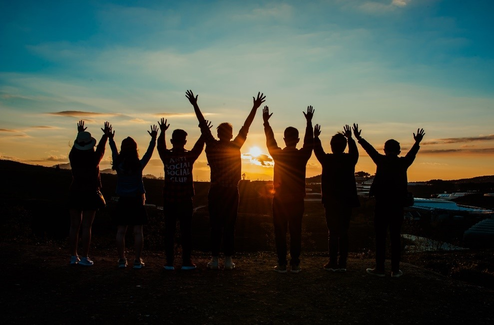 A group of people stretching their arms upwards during the sunset
