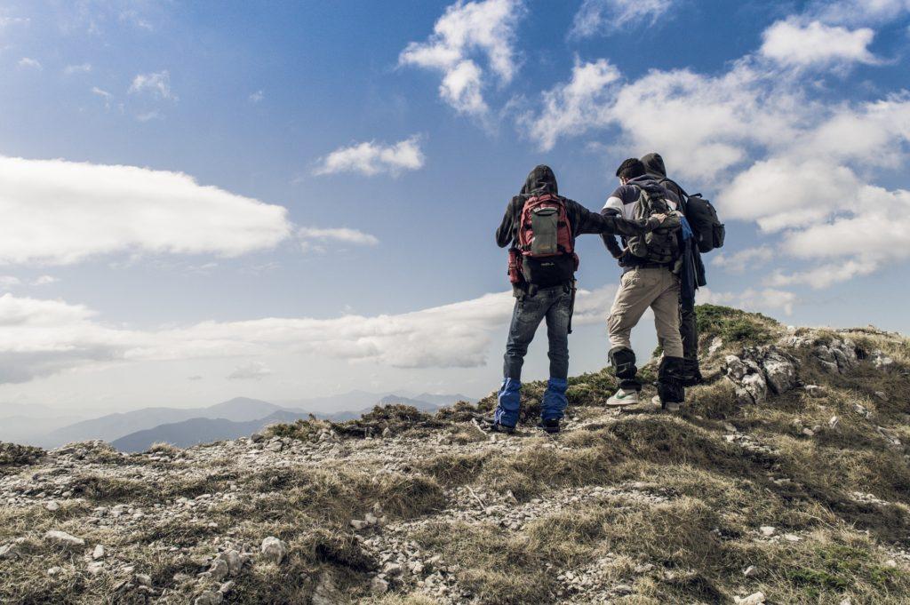 Drei Wanderer, die auf einem Berg die Aussicht anschauen