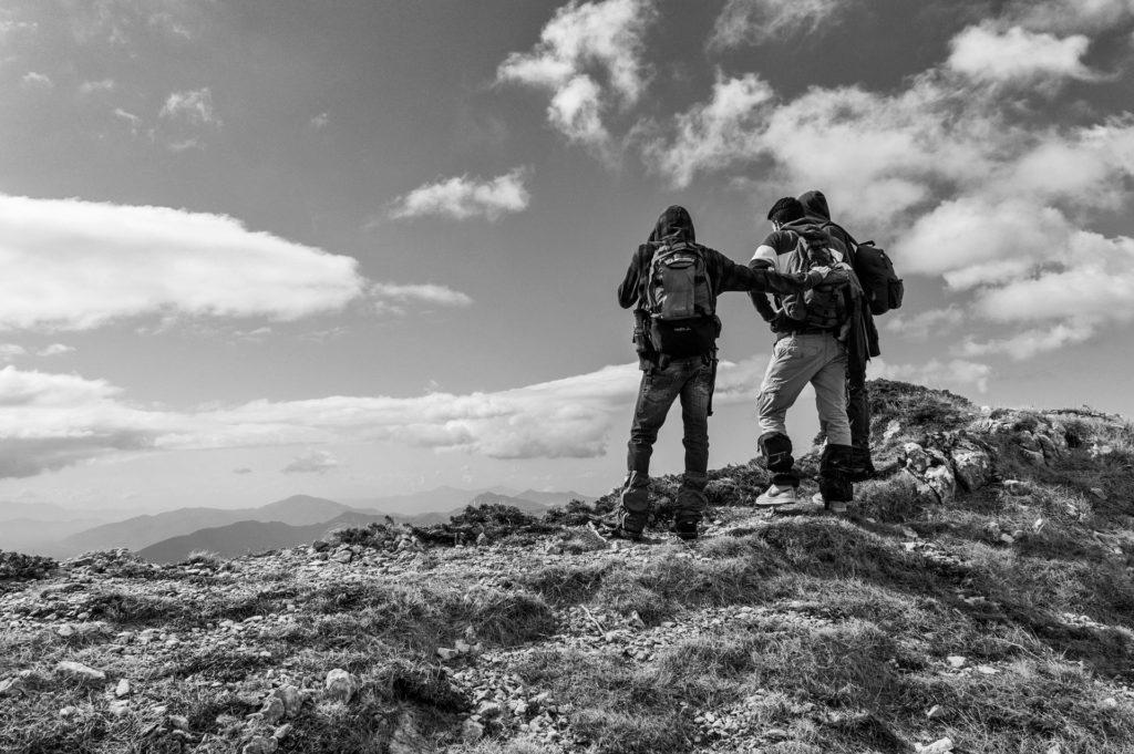 Drei Wanderer, die auf einem Berg die Aussicht anschauen Schwarz-Weiß